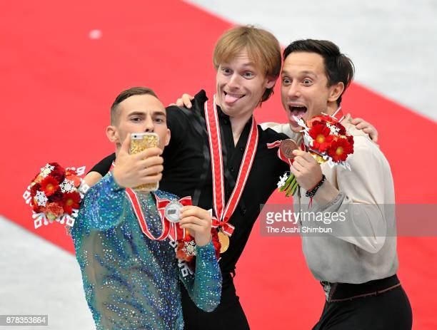 Silver medalist Adam Rippon of United States gold medalist Sergei Voronov of Russia and bronze medalist Alexei Bychenko of Israel take selfie...