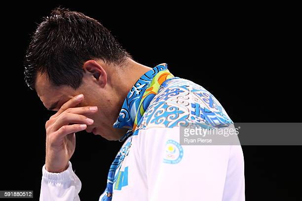 Silver medalist Adilbek Niyazymbetov of Kazakhstan stands on the podium during the medal ceremony for the Men's Light Heavy Boxing event on Day 13 of...