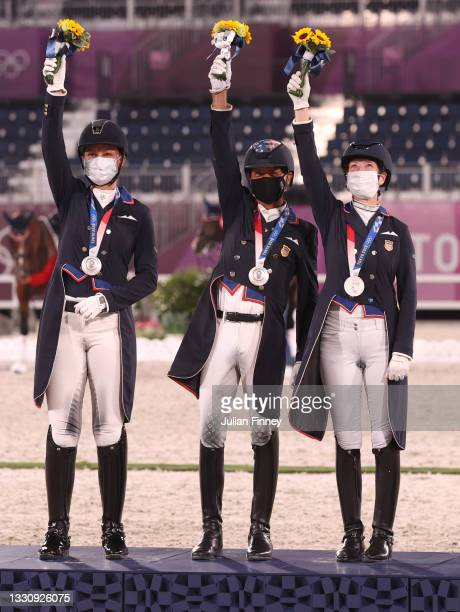 Silver medalist Adrienne Lyle, Steffen Peters, Sabine Schut-Kery of Team USA pose on the podium during the medal ceremony in the Dressage Team Grand...