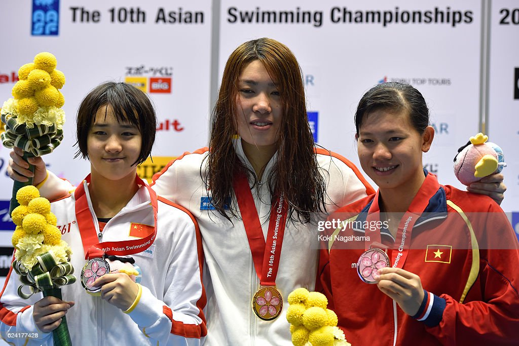 Silver medalist Ai Yanhan of China and Gold medalist Shen Duo of China and Nguyen Thi Anh Vien of Vietnam pose for photographs on the podium after Women's 200m Freestyle final race during the 10th Asian Swimming Championships 2016 at the Tokyo Tatsumi International Swimming Center/Tokyo Metropolitan Swimming Pool on November 18, 2016 in Tokyo, Japan.