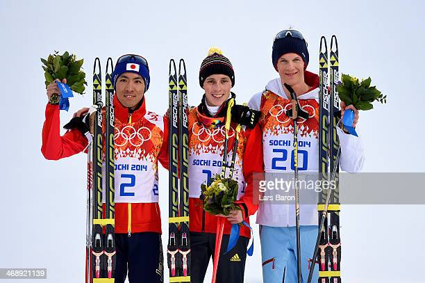 Silver medalist Akito Watabe of Japan gold medalist Eric Frenzel of Germany and bronze medalist Magnus Krog of Norway on the podium during the flower...