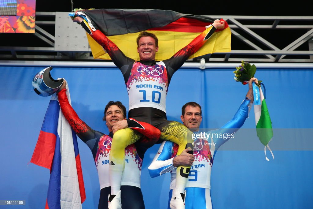 Silver medalist Albert Demchenko of Russia, gold medalist Felix Loch of Germany and bronze medalist Armin Zoeggeler of Italy on the podium during the flower ceremony for the Men's Luge Singles on Day 2 of the Sochi 2014 Winter Olympics at Sliding Center Sanki on February 9, 2014 in Sochi, Russia.