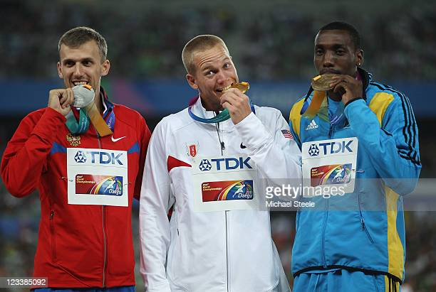 Silver medalist Aleksey Dmitrik of Russia, gold medalist Jesse Williams of United States and bronze medalist Trevor Barry of Bahamas celebrate on the...