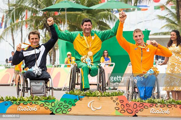 Silver medalist Alessandro Zanardi of Italy Gold medalist Stuart Tripp of South Africa and Tim de Vries of the Netherlands celebrate on the podium at...