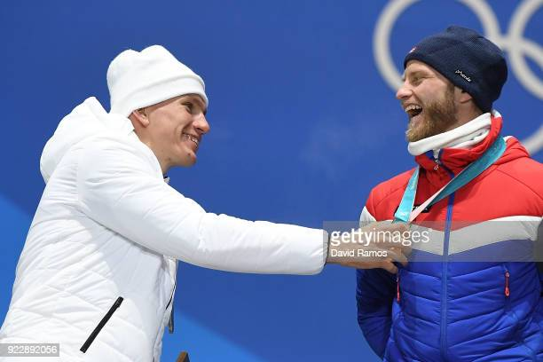 Silver medalist Alexander Bolshunov of Olympic Athlete from Russia pretends to take the gold medal from Martin Johnsrud Sundby of Norway during the...