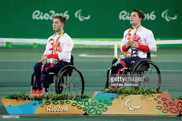 Silver medalist Alfie Hewett of Great Britain and gold medalist Gordon Reid of Great Britain sing the national anthem on the podium at the medal...