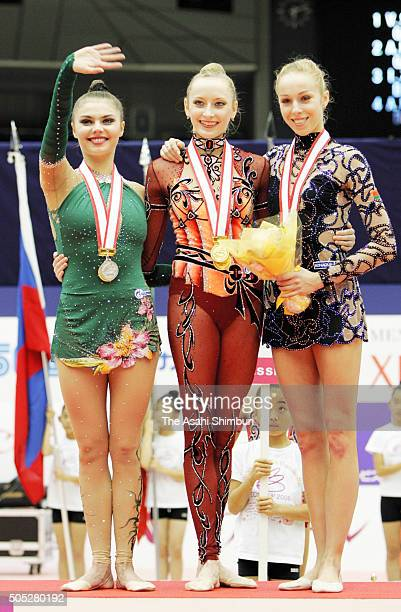 Silver medalist Alina Kabaeva of Russia, gold medalist Vera Sessina of Russia and bronze medalist Inna Zhukova of Belarus pose on the podium at the...