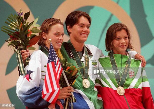 Silver medalist Amanda Beard of the US gold medalist Penny Heyns of South Africa and bronze medalist Agnes Kovas of Hungary smile on the podium after...