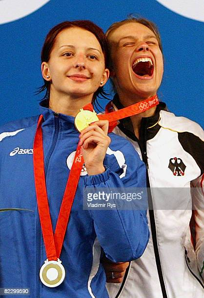 Silver medalist Ana Maria Branza of Romania and gold medalist Britta Heidemann of Germany joke around as they stand on the podium after receiving...