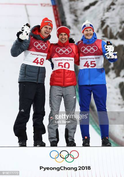Silver medalist Andreas Wellinger of Germany gold medalist Kamil Stoch of Poland and bronze medalist Robert Johansson of Norway celebrate on the...