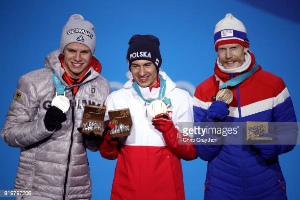 Silver medalist Andreas Wellinger of Germany gold medalist Kamil Stoch of Poland and bronze medalist Robert Johansson of Norway celebrate during the...