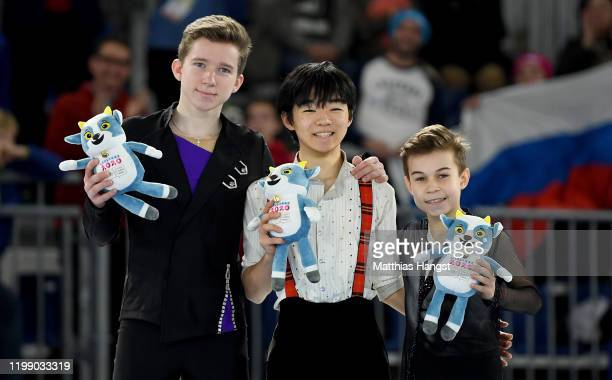 Silver medalist Andrei Mozalev of Russia gold medalist Yuma Kagiyama and bronze medalist Daniil Samsonov of Russia pose for a photo during the mascot...