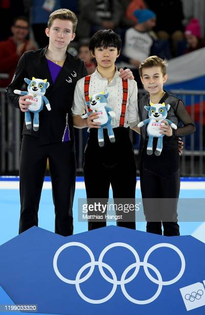 Silver medalist Andrei Mozalev of Russia, gold medalist Yuma Kagiyama and bronze medalist Daniil Samsonov of Russia pose for a photo during the...