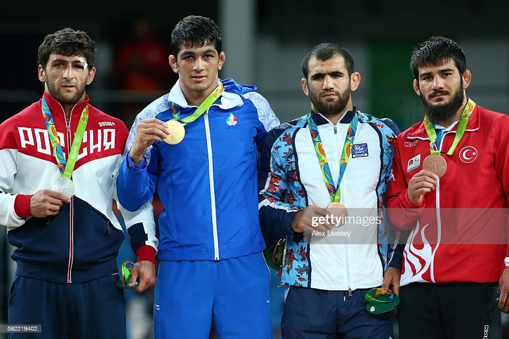 [L-R] Silver medalist Aniuar Geduev of Russia, gold medalist Hassan Aliazam Yazdanicharati of the Islamic Republic of Iran, bronze medalist Jabrayil Hasanov of Azerbaijan and bronze medalist Soner Demirtas of Turkey celebrate on the podium during the medals ceremony after the Men's 74kg Wrestling match on Day 14 of the Rio 2016 Olympic Games at Carioca Arena 2 on August 19, 2016 in Rio de Janeiro, Brazil.
