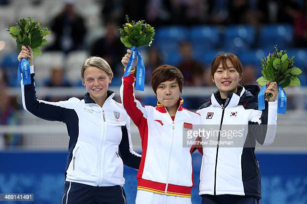 Silver medalist Arianna Fontana of Italy gold medalist Jianrou Li of China and bronze medalist SeungHi Park of Korea during the flower ceremony for...