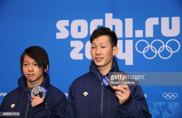 Silver medalist Ayumu Hirano of Japan and bronze medalist Taku Hiraoka of Japan celebrate on the podium during the medal ceremony for Snowboard Men's...