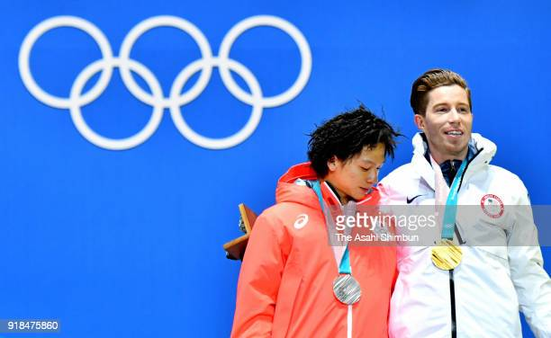 Silver medalist Ayumu Hirano of Japan and gold medalist Shaun White of the United States pose during the medal ceremony for the Snowboard Men's...