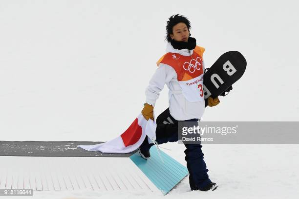 Silver medalist Ayumu Hirano of Japan drags the Japanese flag as he leaves the podium for the Snowboard Men's Halfpipe Final on day five of the...