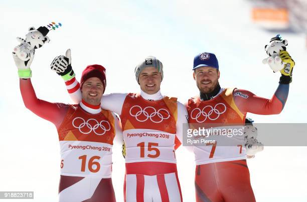 Silver medalist Beat Feuz of Switzerland gold medalist Matthias Mayer of Austria and bronze medalist Kjetil Jansrud of Norway celebrate during the...