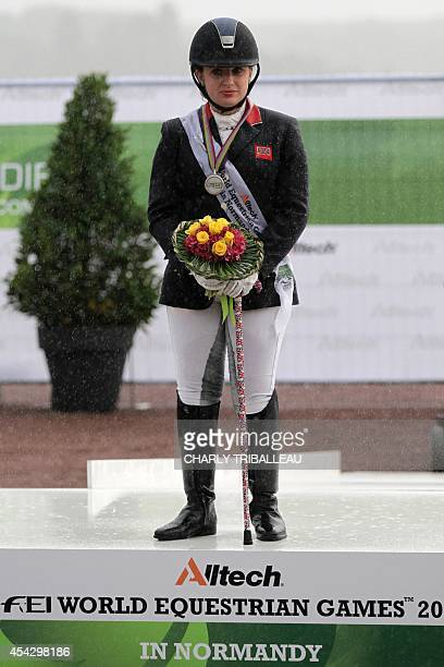 Silver medalist Bristish Natasha Baker celebrates on the podium during the medal ceremony of the Individual Grade II ParaDressage of the 2014 FEI...