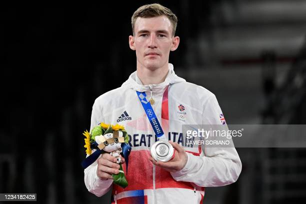 Silver medalist Britain's Bradly Sinden poses on the podium after the taekwondo men's -68kg bouts during the Tokyo 2020 Olympic Games at the Makuhari...