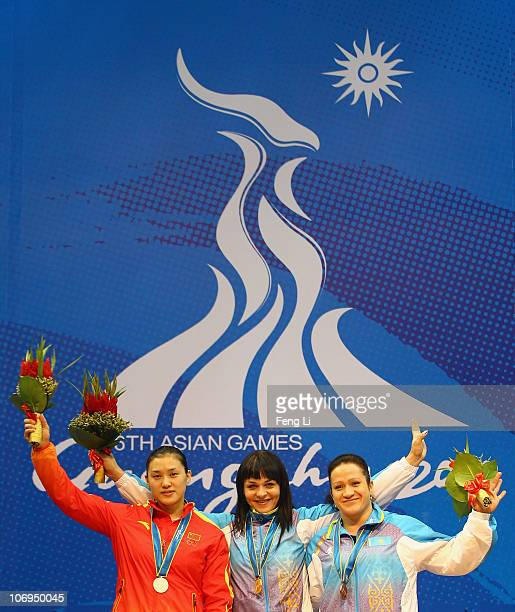 Silver medalist Cao Lei of China gold medalist Svetlana Podobedova of Kazakhstan and bronze medalist Tatyana Khromova of Kazakhstan celebrates during...