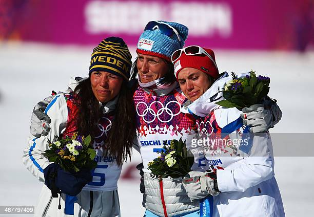 Silver medalist Charlotte Kalla of Sweden gold medalist Marit Bjoergen of Norway and bronze medalist Heidi Weng of Norway celebrate on the podium...