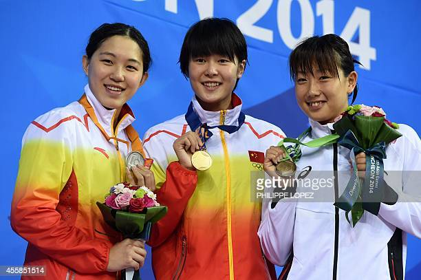Silver medalist China's Bi Yirong gold medalist China's Zhang Yuhan and bronze medallist Japan's Chihiro Igarashi pose with their medals on the...