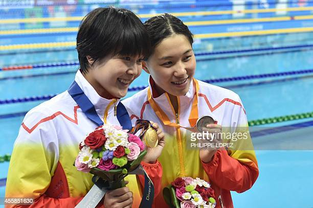Silver medalist China's Bi Yirong poses with gold medallist and teammate China's Zhang Yuhan after the victory ceremony for the women's 400m...