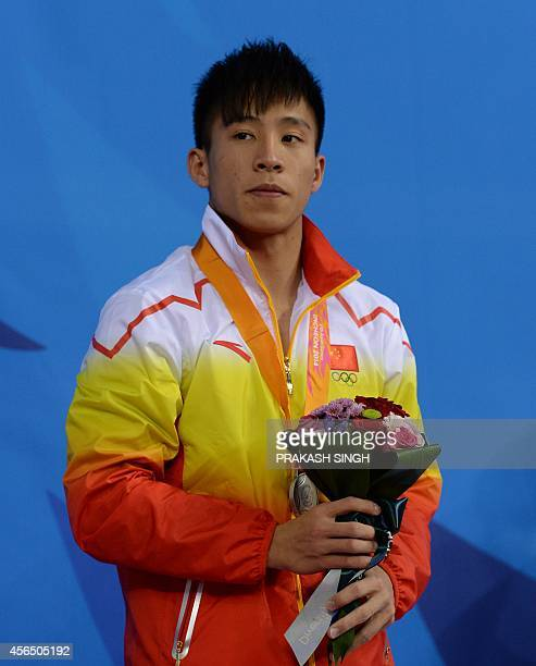 Silver Medalist China's Cao Yuan poses with his medal during the ceremony for the men's 3m springboard diving final of the 2014 Asian Games at the...