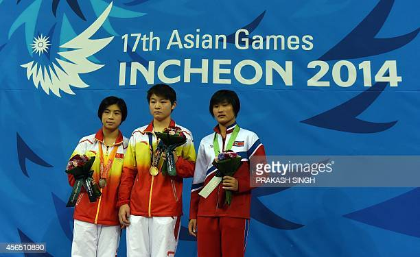 Silver medalist China's Huang Xiaohui gold medalist China's Si Yajie and bronze medalist North Korea's Kim Unhyang pose during the medal ceremony for...