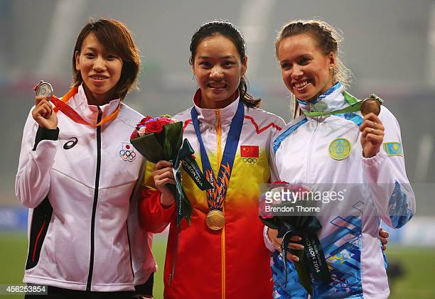 Silver medalist Chisato Fukushima of Japan gold medalist Wei Yongli of China and bronze medalist Olga Safronova of Kazakhstan pose on the podium...
