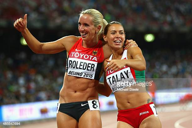 Silver medalist Cindy Roleder of Germany and bronze medalist Alina Talay of Belarus celebrate after the Women's 100 metres hurdles final during day...
