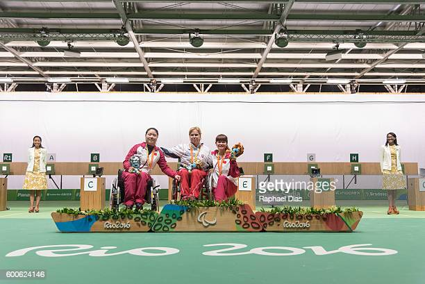 Silver medalist Cuiping Zhang gold medalist Veronika Vodovicova and bronze medalist Yaping Yan celebrate on the podium at the medal ceremony for the...