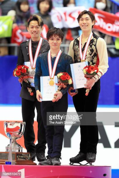 Silver medalist Daisuke Takahashi gold medalist Shoma Uno and bronze medalist Keiji Tanaka pose on the podium at the medal ceremony for the men's...