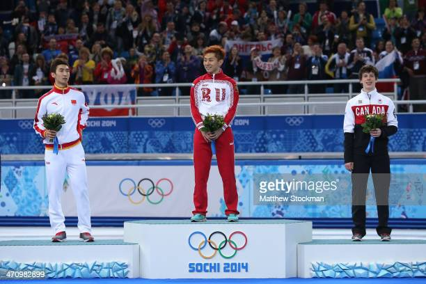 Silver medalist Dajing Wu of China gold medalist Victor An and bronze medalist Charle Cournoyer of Canada celebrate on the podium during the flower...