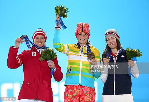 Silver medalist Daniela Iraschko-Stolz of Austria, gold medalist Carina Vogt of Germany and bronze medalist Coline Mattel of France celebrate on the...