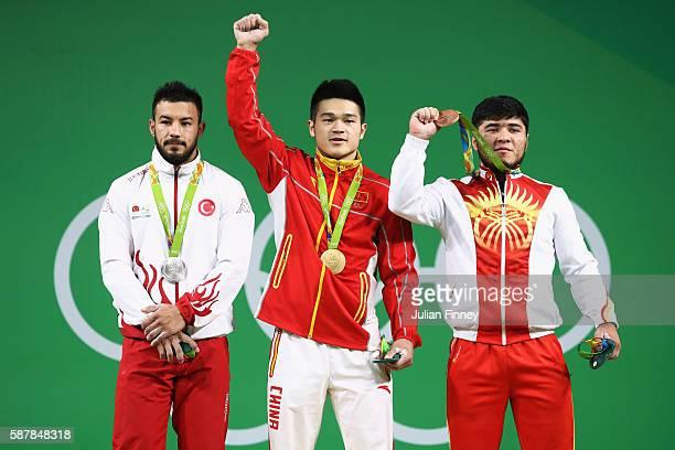 Silver medalist Daniyar Ismayilov of Turkey gold medalist Zhiyong Shi of China and bronze medalist Izzat Artykov of Kyrgyzstan stand on the podium...