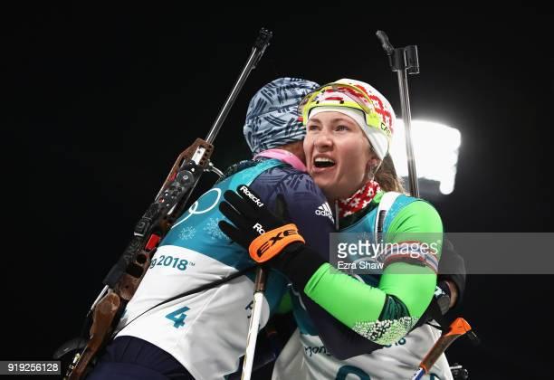 Silver medalist Darya Domracheva of Belarus and gold medalist Anastasiya Kuzmina of Slovakia embrace after the Women's 125km Mass Start Biathlon on...