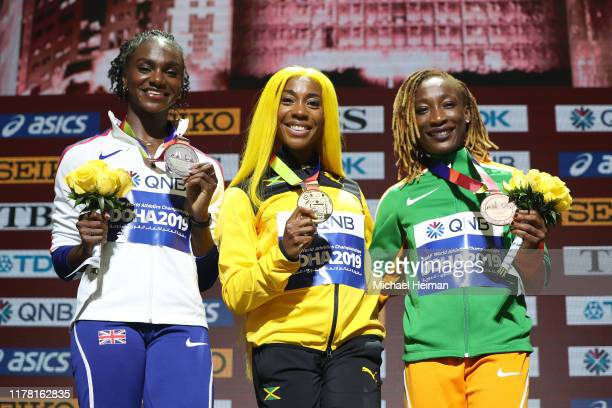 Silver medalist Dina Asher-Smith of Great Britain, gold medalist Shelly-Ann Fraser-Pryce of Jamaica and bronze medalist Marie-Josée Ta Lou of the...