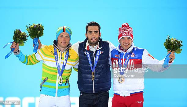 Silver medalist Erik Lesser of Germany, gold medalist Martin Fourcade of France and bronze medalist Evgeniy Garanichev of Russia celebrate on the...