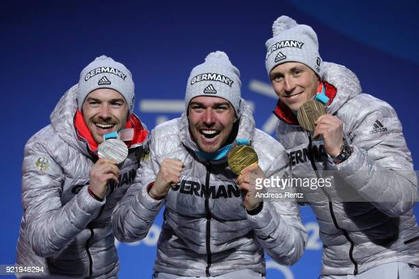 Silver medalist Fabian Riessle of Germany, gold medalist Johannes Rydzek of Germany and bronze medalist Eric Frenzel of Germany celebrate during the...