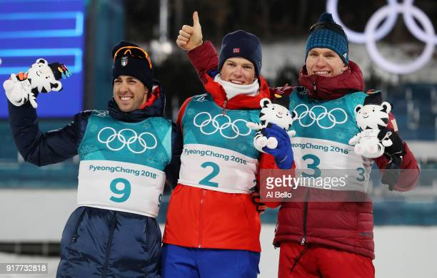 Silver medalist Federico Pellegrino, gold medalist Johannes Hoesflot Klaebo of Norway and Alexander Bolshunov of Olympic Athlete from Russia pose...