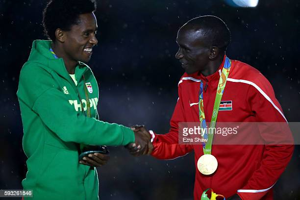 Silver medalist Feyisa Lilesa of Ethiopia and gold medalist Eliud Kipchoge of Kenya shake hands during the medal ceremony for the Men's Marathon...