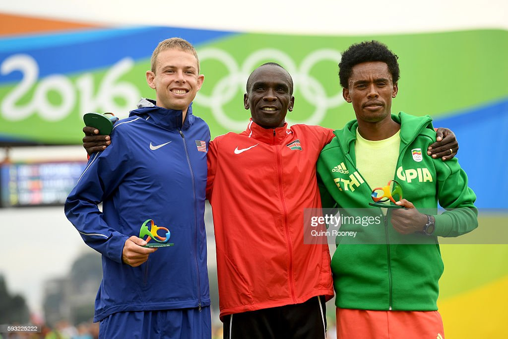 Silver medalist Feyisa Lilesa of Ethiopia, gold medalist Eliud Kipchoge of Kenya and bronze medalist Galen Rupp of the United States celebrate on the podium during victory ceremony after the Men's Marathon on Day 16 of the Rio 2016 Olympic Games at Sambodromo on August 21, 2016 in Rio de Janeiro, Brazil.