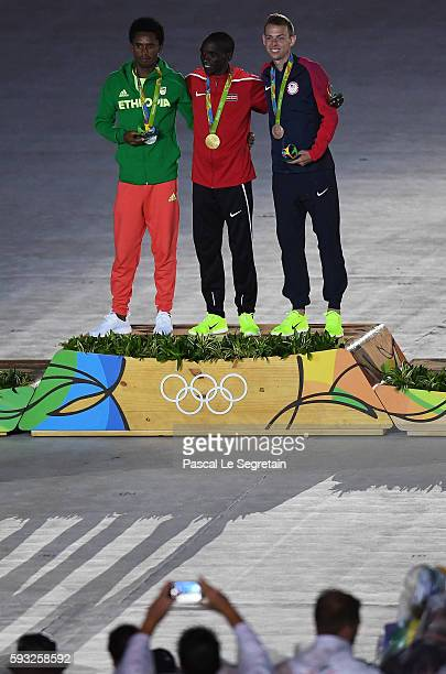 Silver medalist Feyisa Lilesa of Ethiopia gold medalist Eliud Kipchoge of Kenya and bronze medalist Galen Rupp of the United States celebrate on the...