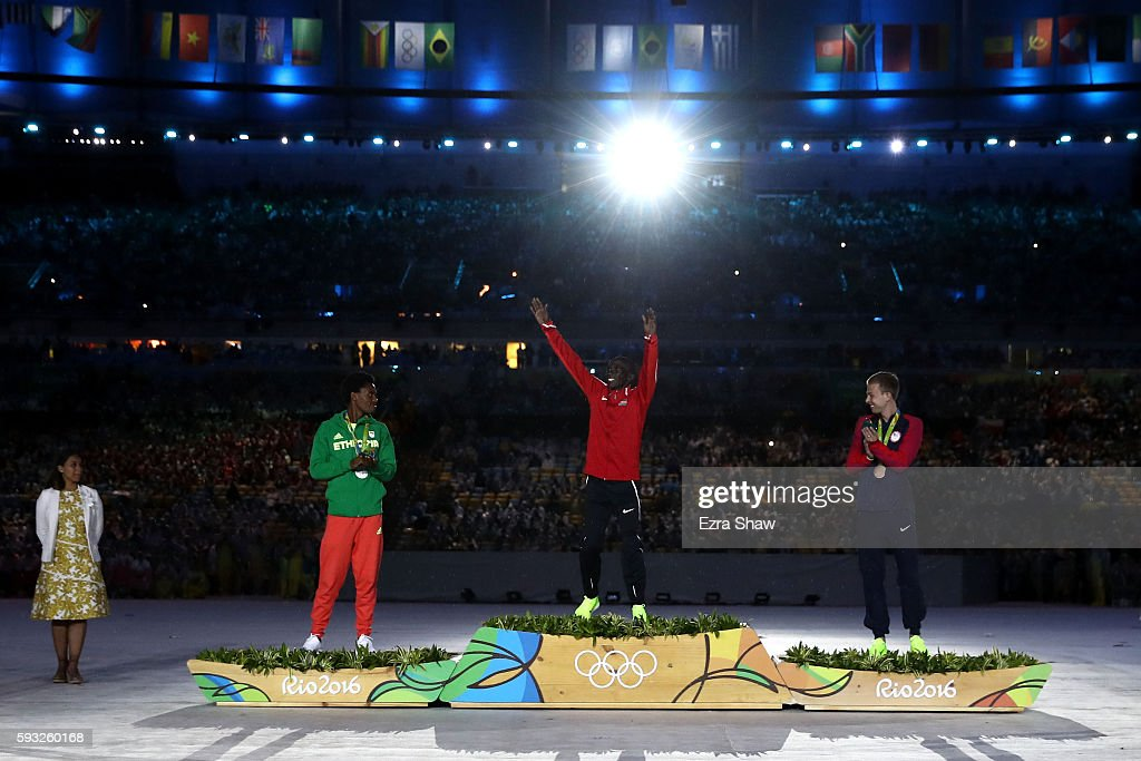 Silver medalist Feyisa Lilesa of Ethiopia, gold medalist Eliud Kipchoge of Kenya and bronze medalist Galen Rupp of the United States celebrate during the medal ceremony for the Men's Marathon during the Closing Ceremony on Day 16 of the Rio 2016 Olympic Games at Maracana Stadium on August 21, 2016 in Rio de Janeiro, Brazil.