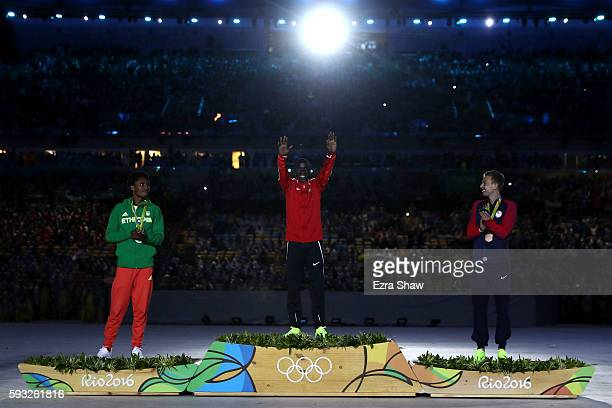 Silver medalist Feyisa Lilesa of Ethiopia gold medalist Eliud Kipchoge of Kenya and bronze medalist Galen Rupp of the United States celebrate during...