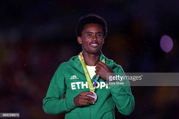 Silver medalist Feyisa Lilesa of Ethiopia stands on the podium during the medal ceremony for the Men's Marathon during the Closing Ceremony on Day 16...