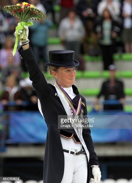 Silver medalist German Helen Langehanenberg poses on the podium during the medals ceremony of the Individual Dressage Grand Prix of the 2014 FEI...